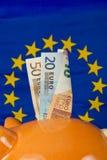 有欧洲笔记的存钱罐,欧盟在背景中下垂 免版税库存照片