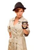 有正式徽章的严肃的女性探员在白色的军用防水短大衣 免版税库存照片