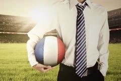 有正式衣服的人拿着球在领域 免版税库存图片