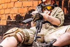有步枪的军队女孩在伪装在都市场面穿衣,得到休息Croped画象,关闭  免版税库存图片