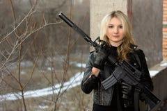 有步枪的害怕的女孩 免版税图库摄影