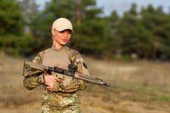 有步枪的美丽的妇女别动队员在伪装 免版税库存照片