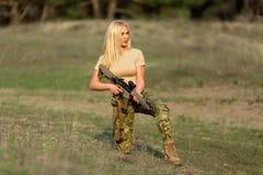 有步枪的美丽的妇女别动队员在伪装 库存图片