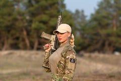 有步枪的美丽的妇女别动队员在伪装 免版税图库摄影