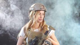 有步枪的逗人喜爱的狙击手妇女在站立在军用成套装备的手上在黑暗中 股票视频