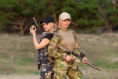 有武器的美丽的妇女别动队员在伪装 免版税库存图片
