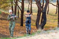 有武器的美丽的妇女别动队员在伪装 免版税库存照片