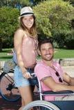 有残疾伙伴的妇女轮椅的在公园 库存图片