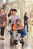 有残疾母亲的妇女在Livat商城,北京,中国的轮椅的 免版税库存照片