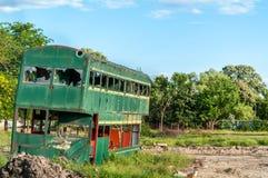 有残破和被打碎的玻璃窗的老被放弃的绿色双层公共汽车,损坏和听任铁锈 库存图片