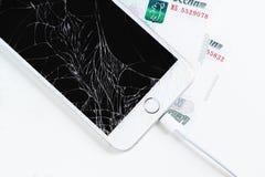 有残破的显示的手机和在白色背景的俄国金钱 免版税库存照片