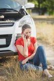 有残破的汽车的叫哀伤的少妇服务拖曳她的运输 图库摄影