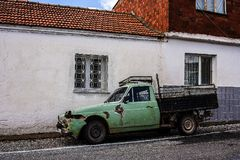 有残破的装甲的一辆老被毁坏的蓝绿色卡车在街道停放了 免版税库存图片