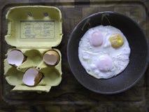 有残破的壳和煎蛋的蛋盒在煎锅 库存图片