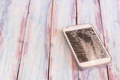 有残破的屏幕的智能手机在木桌上 库存图片