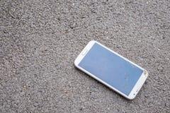 有残破的屏幕的电话在街道上 免版税图库摄影