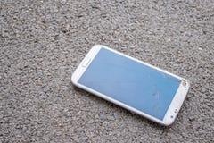 有残破的屏幕的电话在街道上 库存图片