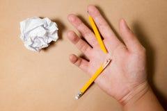 有残破的铅笔和被弄皱的纸的手 企业失望、工作压力和不合格的检查概念 库存照片