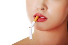 有残破的香烟的少妇在嘴 库存照片