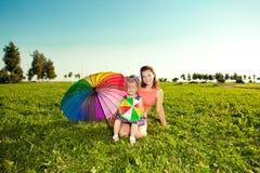 有母亲举行在p的彩虹伞的逗人喜爱的小女孩 免版税库存照片
