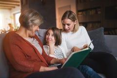 有母亲和祖母的一个小女孩在家 免版税库存照片
