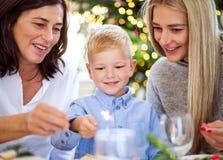 有母亲和祖母藏品的一个小男孩闪耀在圣诞节时间 免版税库存照片