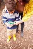 有母亲审查的昆虫的男孩与放大镜 免版税图库摄影