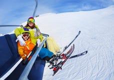 有母亲推力的小滑雪者男孩在山 库存图片