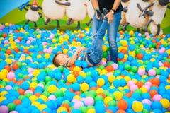 有母亲的一个男孩在有许多一点色的球的使用的屋子 库存照片