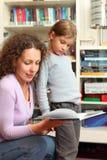 有母亲的女儿在屋子里读了书 免版税库存照片