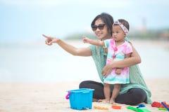 有母亲的女婴与玩具的海滩戏剧的在沙子 免版税库存照片