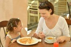 有母亲的小女孩吃 免版税图库摄影