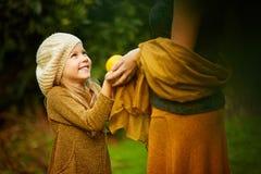 有母亲的愉快的女孩在绿色庭院里 免版税库存照片