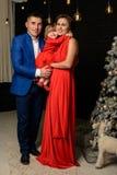 有母亲的父亲和他们的在一个圣诞树妈妈旁边的女儿身分有红色礼服的女儿的 库存图片