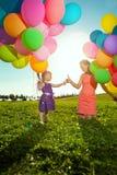 有母亲的美丽的小女孩上色了气球和彩虹u 图库摄影