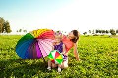 有母亲的逗人喜爱的小女孩上色了气球和彩虹umbrel 图库摄影
