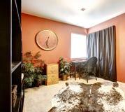 有母牛皮肤地毯的明亮的橙色室 库存照片