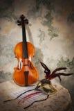 有比分的在一个石墙上的小提琴和面具 免版税库存图片
