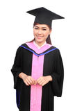 有毕业方帽与长袍的妇女 免版税库存图片