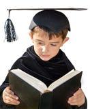 有毕业盖帽的逗人喜爱的孩子毕业生 免版税图库摄影