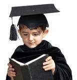 有毕业盖帽的逗人喜爱的孩子毕业生 免版税库存图片
