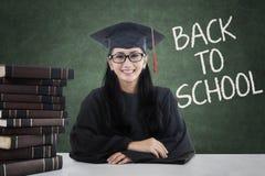 有毕业长袍的聪明的学生回到学校 免版税图库摄影