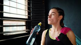 有毛巾的健身妇女在从锻炼和饮用水的健身房休假从瓶 股票视频