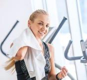 有毛巾的可爱的女性在踏车锻炼以后 库存照片
