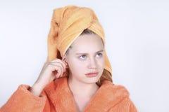 有毛巾的女孩在他的有棉花棒的顶头清洁耳朵 免版税库存图片