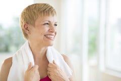 有毛巾的妇女在脖子上嘲笑健身房的 免版税图库摄影