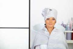 有毛巾的少妇在坐在发廊的头。 免版税图库摄影