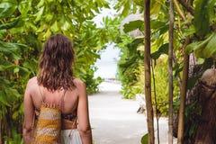 有毛巾的年轻女人走到在一个热带目的地的海滩的 免版税库存图片