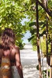 有毛巾的年轻女人走到在一个热带目的地的海滩的 免版税图库摄影