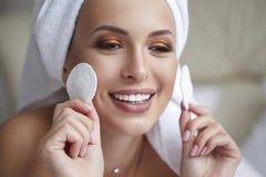 有毛巾的年轻美丽的微笑的妇女在她的拿着化装棉的头 皮肤护理、温泉和秀丽治疗 构成去除 库存照片